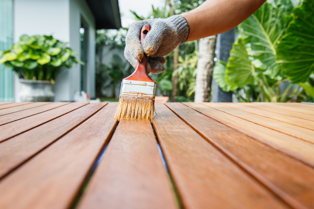 Hand with glove, paintbrush, staining outdoor tabletop, home improvement