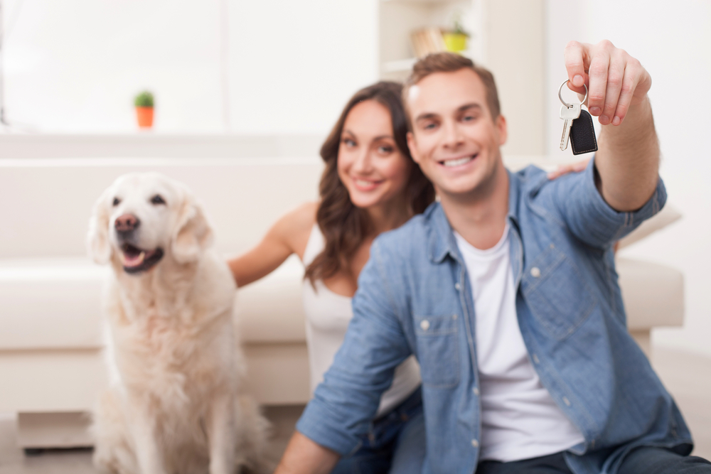 Happy couple holding up house keys, with dog, pet-friendly rental property