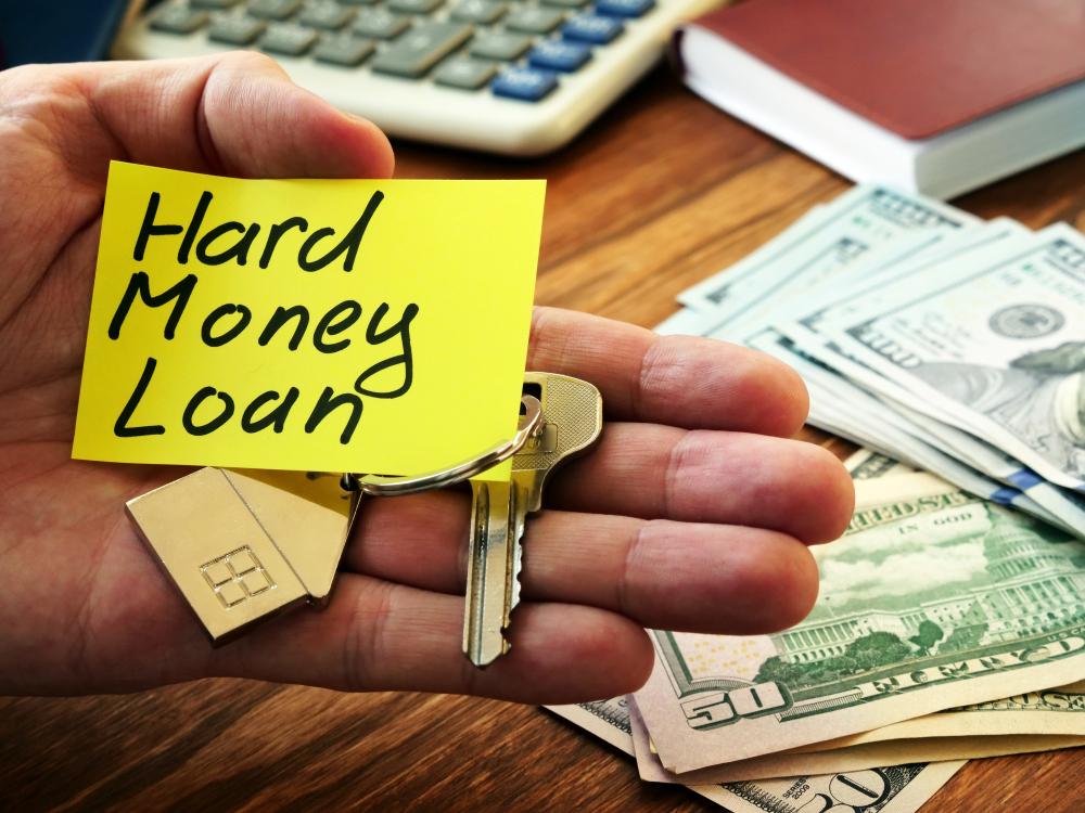 hand holding hard money loan sign, key, money, calculator