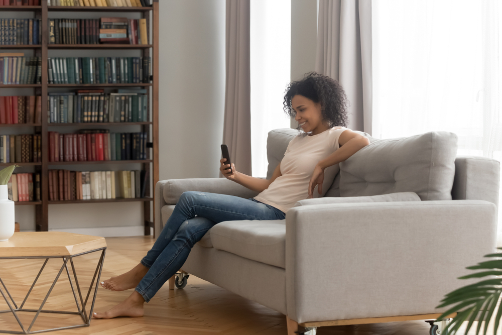 young woman on sofa with cell phone, modern home, bookshelf